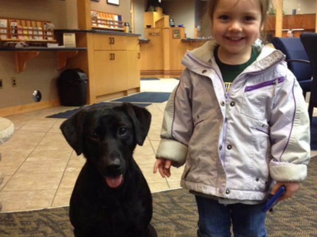 A child standing next to a black dog