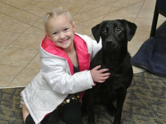 A girl hugging a black dog