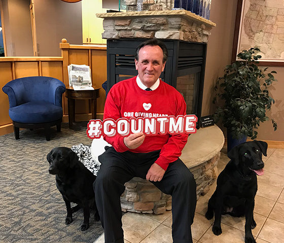 A man sitting with two dogs and holding a #countme sign