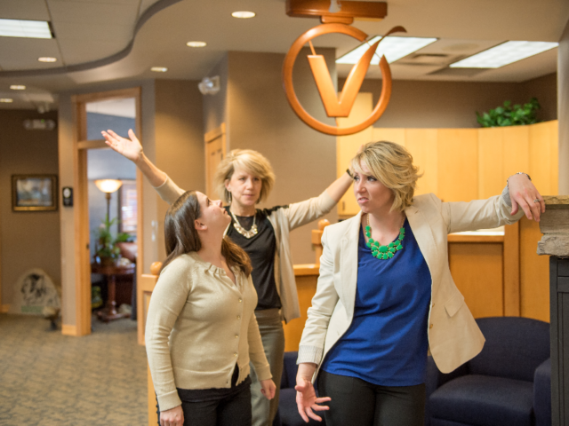 3 women doing poses in the VISIONBank office
